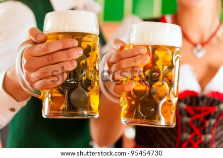 Young man and woman in traditional Tracht with beer glass in brewery, in front of brewing kettle