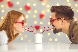 Young man and woman leaning over table at home or in cafe and drinking from one cup through heart-shaped straws. Cute and funny couple moments. Having fun on Saint Valentine's Day. Sharing happiness