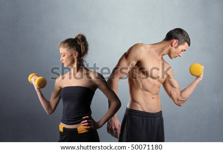 Young man and woman lifting weights