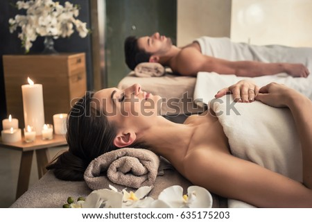 Young man and woman lying down on massage beds at Asian luxury spa and wellness center - Shutterstock ID 635175203