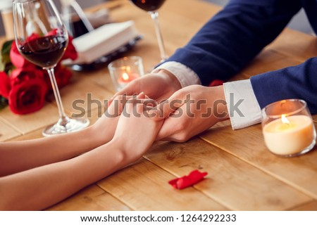 Young man and woman on date in restaurant sitting at table covered with rose petals close-up drinking red wine holding hands