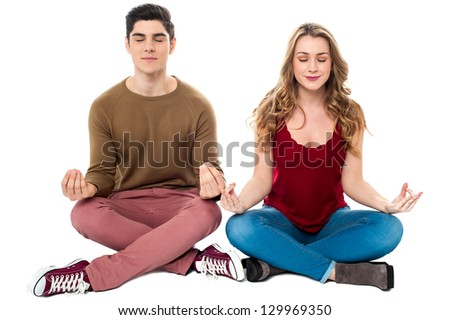 Young man and woman on white background meditating peacefully.