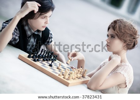 Young man and woman playing chess. Soft white colors and shallow dof.