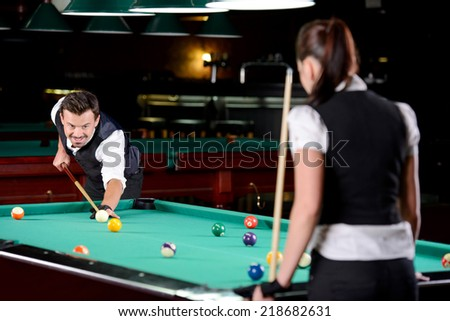 Young man and woman playing professional billiards in the dark billiard club