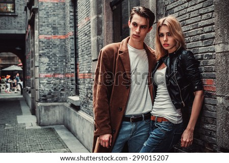 Young man and woman posing of the street with brick walls. Fashion vogue. #299015207