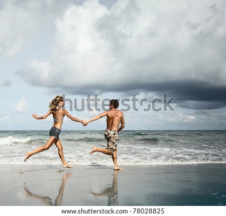 Young man and woman running together on wet sand by sea edge on dark sky background