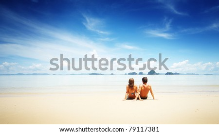 Young man and woman sitting on sand by sea and looking to somewhere
