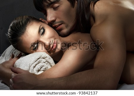 Young man and woman sleeping in white bed