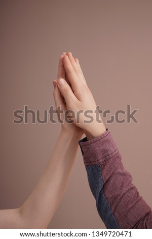 Young man and woman touching palms against color background #1349720471