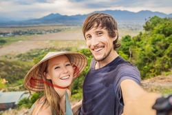 Young man and woman tourist in a traditional Vietnamese hat travels to Vietnam