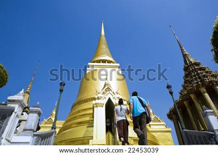 Young man and woman travel in Grand Palace Bangkok - stock photo