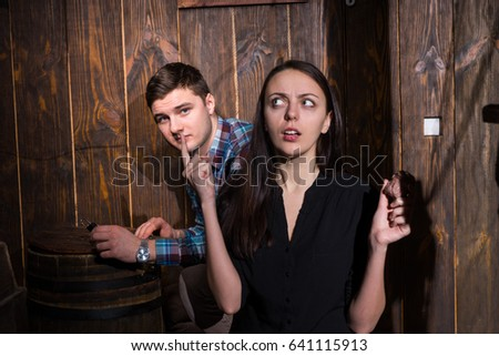 Young man and woman trying to solve a conundrum to get out of the trap, escape the room game concept #641115913