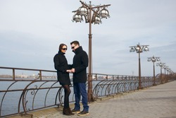 Young man and woman walking along the waterfront, uys in glasses, look at their hands