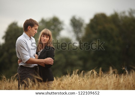 young man and woman walking in a field of wheat