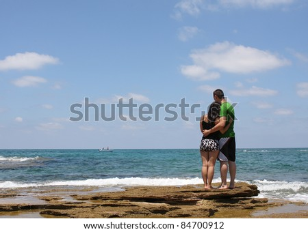 Young man and woman walking on the shore - stock photo