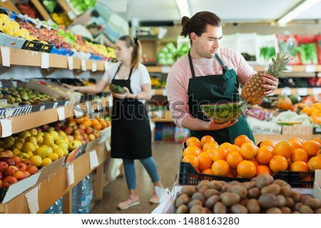 Young man and woman wearing aprons offering fresh fruits on the supermarket #1488163280