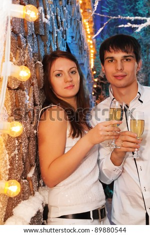 Young man and woman wearing white shirts with glasses of champagne stand near stack of wood and look at camera