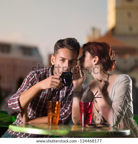 young man and woman whispering something at a man's year, on a terrace