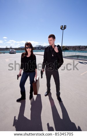 Young man and woman with a briefcase and guns