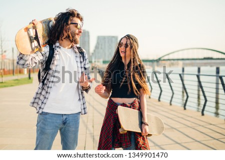 Young man and woman with skateboards, enjoying the sunny day next on a walkway next to the river. #1349901470