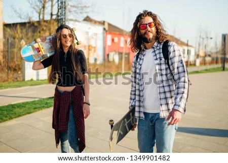 Young man and woman with skateboards, enjoying the sunny day next on a walkway next to the river. #1349901482