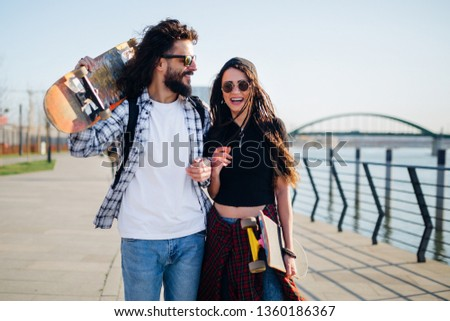 Young man and woman with skateboards, enjoying the sunny day next on a walkway next to the river. #1360186367