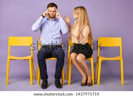 young man and young blonde woman having conflict, face left. and waiting for job interview