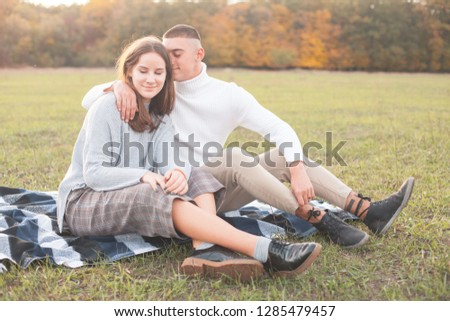 Young man and young woman are sitting on the grass field.