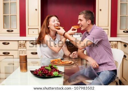 Young man and young woman feed pizza to each other
