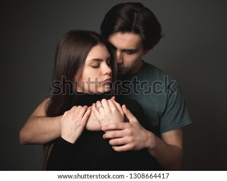 Young man and young woman hugging in studio
