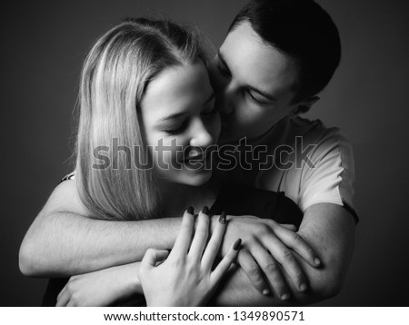 Young man and young woman in studio. Black and white.