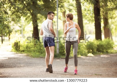 Young man and young woman jogging in park