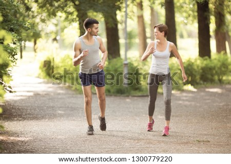 Young man and young woman jogging together in park