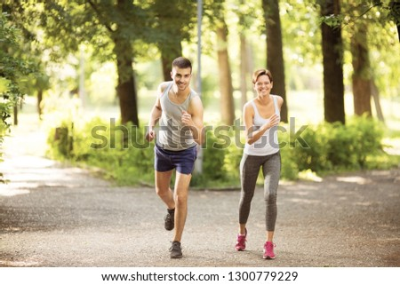 Young man and young woman jogging together outdoors #1300779229
