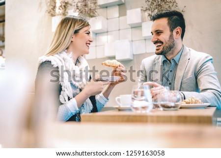 Young man and young woman sitting at cafe and talking with smile. They drinking coffee and having breakfast.