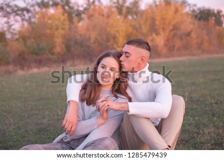 Young man and young woman sitting on the grass at sunset