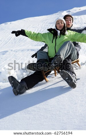 Young man and young woman sledding in snow