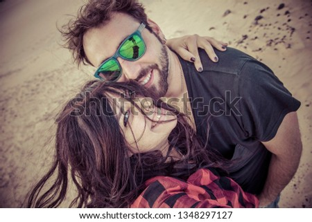young man and young woman take a selfie picture of themselves on the sand, they are very happy