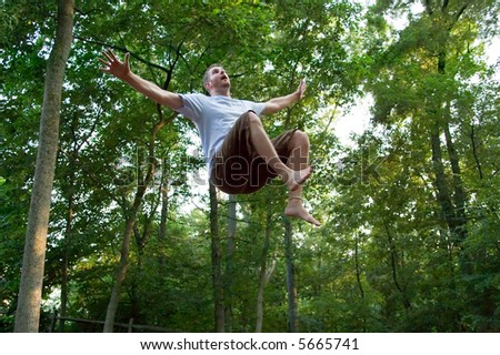 Young man appears to be floating in mid-air, looking upward, with startled expression. Is it an alien abduction or is he falling from the sky?