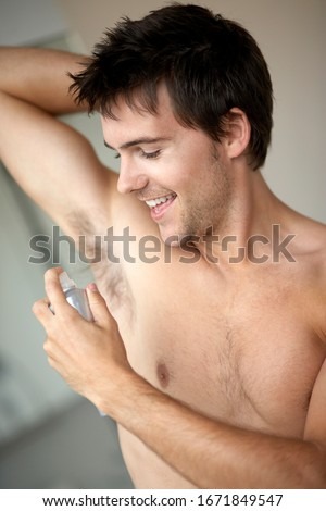 Young man applying de-odorant anti-perspirant in the morning