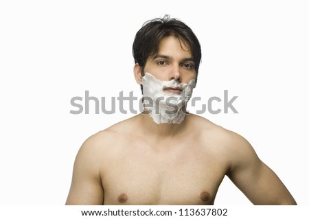 Young man applying shaving cream on his face