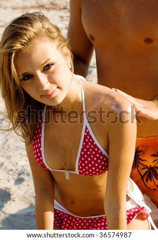 Young man applying suntan cream to his girlfriend's back