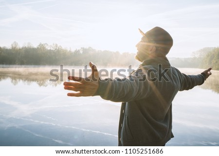 Young man arms outstretched by the lake at sunrise enjoying freedom and life, people travel wellbeing concept. Shot in France, Europe. Foto stock ©