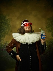 Young man as a medieval knight in red cap on dark studio background. Portrait of male model in retro costume. Holding a drink. Human emotions, comparison of eras and facial expressions concept.