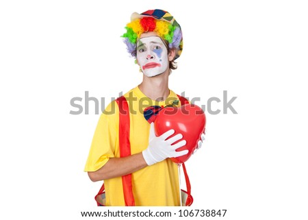 Young man as clown with red balloon