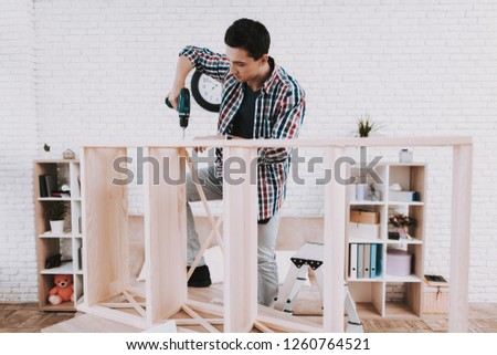 Young Man Assembling Wooden Bookshelf at Home. Wooden Bookcase. Selfmade Furniture. Man and Hobby. White Room. Engineer with Tool. Young Man at Home. Homemade Decoration. Modern Furniture. #1260764521