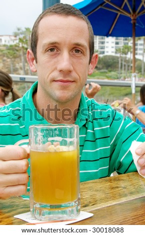 Young man at an outdoor restaurant holding a glass of beer