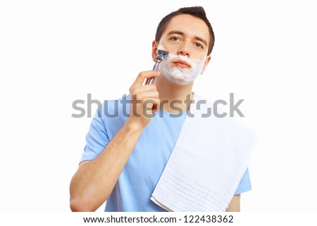 Young man at home shaving himself in the morning