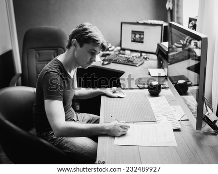 Young man at home using a computer, freelance developer and designer working at home, black and white photo