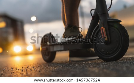 Young man at night with electric scooter or e-scooter in the city, Electric urban transportation concept image